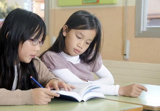 本を見る女子児童たち